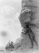 San Ildefonso man peering from behind large rock formation, c1927. Photograph by Edward Curtis (1868-1952).