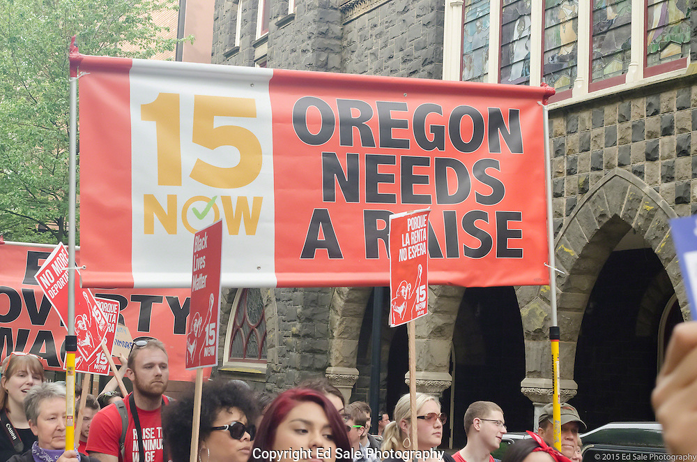 Demonstrator in 2015 May Day rally and march in Portland, Oregon hold a banner supporting a state-wide minimum wage increase in Oregon.