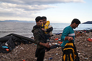 Newly arrived migrants and refugees to Greece, stand on a beach on the northern coastline of Lesvos island.