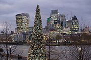 Christmas tree lights compliments lighting on in buildings and skyscrapers in the City of London in London, England, United Kingdom.