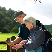 A pair of elderly hikers refer to their map, Rievaulx Abbey, North Yorkshire, UK