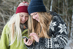 Teenage girls using the smartphone and smiling, Bavaria, Germany