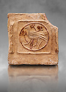 6th-7th Century Eastern Roman Byzantine  Christian Terracotta tiles depicting a bird - Produced in Byzacena -  present day Tunisia. <br /> <br /> These early Christian terracotta tiles were mass produced thanks to moulds. Their quadrangular, square or rectangular shape as well as the standardised sizes in use in the different regions were determined by their architectonic function and were designed to facilitate their assembly according to various combinations to decorate large flat surfaces of walls or ceilings. <br /> <br /> Byzacena stood out for its use of biblical and hagiographic themes and a richer variety of animals, birds and roses. Some deer and lions were obviously inspired from Zeugitana prototypes attesting to the pre-existence of this province's production with respect to that of Byzacena. The rules governing this art are similar to those that applied to late Roman and Christian art with, in the case of Byzacena, an obvious popular connotation. Its distinguishing features are flatness, a predilection for symmetrical compositions, frontal and lateral representations, the absence of tridimensional attitudes and the naivety of some details (large eyes, pointed chins). Mass production enabled this type of decoration to be widely used at little cost and it played a role as ideograms and for teaching catechism through pictures. Painting, now often faded, enhanced motifs in relief or enriched them with additional details to break their repetitive monotony.<br /> <br /> The Bardo National Museum Tunis, Tunisia. Against a grey art background.