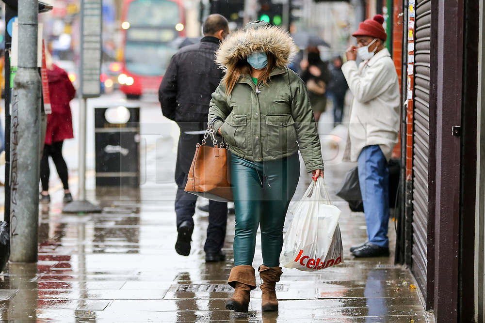 © Licensed to London News Pictures. 14/11/2020. London, UK. A shopper wearing a face covering is caught in the rain in north London. The Met Office has issued a yellow weather warning for the UK for heavy rain and strong winds, as up to 20 days worth of rain is expected to fall in the next few days. Photo credit: Dinendra Haria/LNP