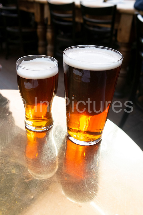 A pint and a half glass of ale on a brass table in a pub in London, United Kingdom.