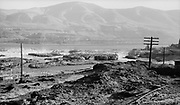 0015-07. View of Celilo falls area from Celilo Indian village about 1955. On the right is the automobile bridge over the canal, and the parking lot connecting with fishing platforms on the Oregon shore at Horseshoe falls.