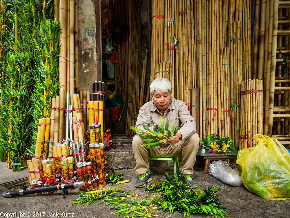 """24 DECEMBER 2017 - HANOI, VIETNAM: A man trims bamboo is shop in the old quarter of Hanoi. The old quarter is the heart of Hanoi, with narrow streets and lots of small shops but it's being """"gentrified"""" because of tourism and some of the shops are being turned into hotels and cafes for tourists and wealthy Vietnamese.           PHOTO BY JACK KURTZ"""