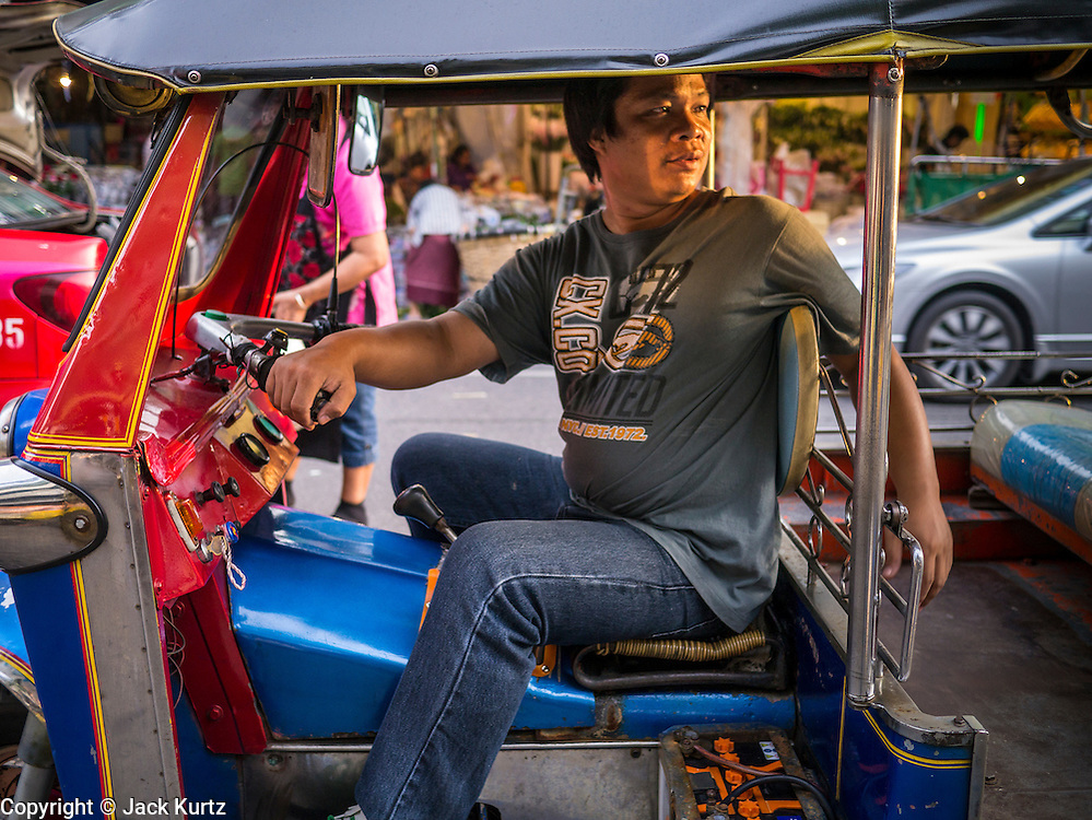 19 OCTOBER 2012 - BANGKOK, THAILAND:   A tuk-tuk driver in his tuk-tuk at the Bangkok Flower Market. (Tuk-tuks are three wheeled taxi common in developing cities in Asia.) The Bangkok Flower Market (Pak Klong Talad) is the biggest wholesale and retail fresh flower market in Bangkok.  The market is busiest between 3:30AM and 6AM. Thais grow and use a lot of flowers. Some, like marigolds and lotus, are used for religious purposes. Others are purely ornamental.          PHOTO BY JACK KURTZ