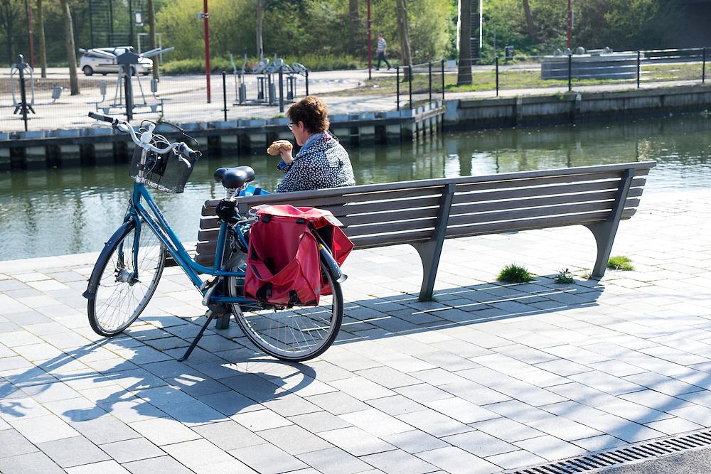 In Nieuwegein genieten mensen langs het Merwedekanaal van het mooie lenteweer door even te pauzeren tijdens eens fietstocht op een bankje en een broodje te eten.<br /> <br /> In Nieuwegein people are enjoying the nice weather. A woman is sitting on a bench next to the Merwedekanaal to pause from a bike tour and is eating a sandwich.