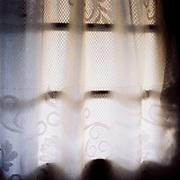 A net curtain hangs at a farmhouse window, Botiza, Maramures, Romania