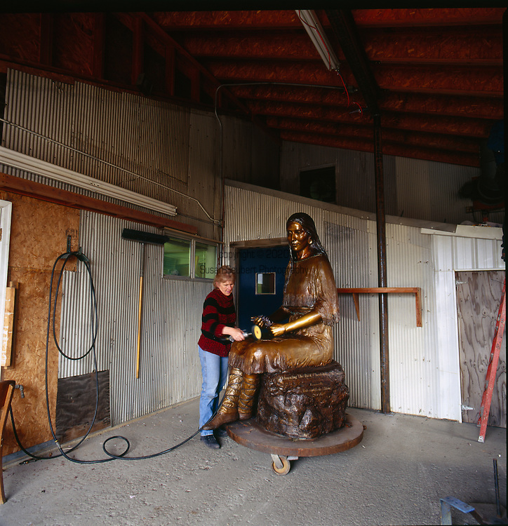 Valley Bronze Studio in Joseph, Oregon.<br /> Valley Bronze is a  fine art foundry in the Pacific Northwest. Working in all metals, including stainless and silver, they are able to undertake a full range of casting projects, from small editions to monuments. Pictured here is a woman working at the foundry in Joseph putting the finishing touches on a larger than life size sculpture of Sacagawea.