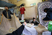 Harjeza Sedighi Fard, 75, seated, and his family sort hand block-printed cotton fabrics in the bazaar at Isfahan, Iran.