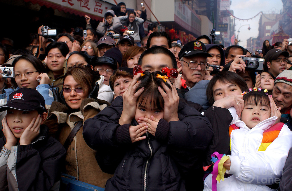 A crowd of people covers their ears as a large set of firecrackers are set off during Chinese New Year celebrations in Chinatown in New York Wednesday 9 February 2005.