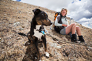 Kate Clark and her dog Zapata relax in the alpine above Parika Lake, Never Summer Wilderness, Colorado.