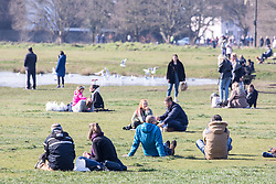 © Licensed to London News Pictures. 07/03/2021. London, UK. Members of the public enjoy a picnic on Wimbledon Common in the sunshine this afternoon. From Monday, 8th March 2021 two friends will be allowed to socialise out side of their household for a coffee or picnic for the first time in months. England will begin Stage1 of the easing of lockdown tomorrow, with children returning to school, care homes allowing a visitor and friends being allowed to socialise out side of their household. However, pubs, shops and restaurants will still remain closed. Photo credit: Alex Lentati/LNP