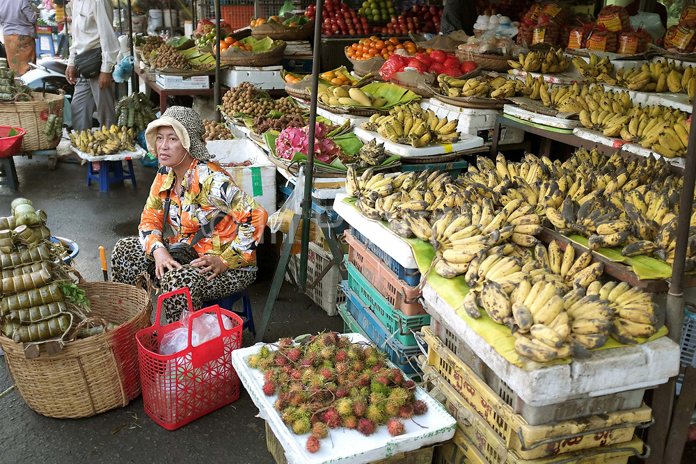 Vendor selling sticky rice wrapped in banana leaves in front of the fruit stall at Kandal morning market in Phnom Penh, the capital city of Cambodia. A large variety of local products are available for sale in fresh markets all over Cambodia, all being sold on small individual stalls.