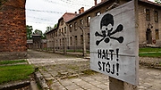 Electrified fence and warning sign at the Auschwitz-Birkenau concentration camp, Auschwitz, Poland