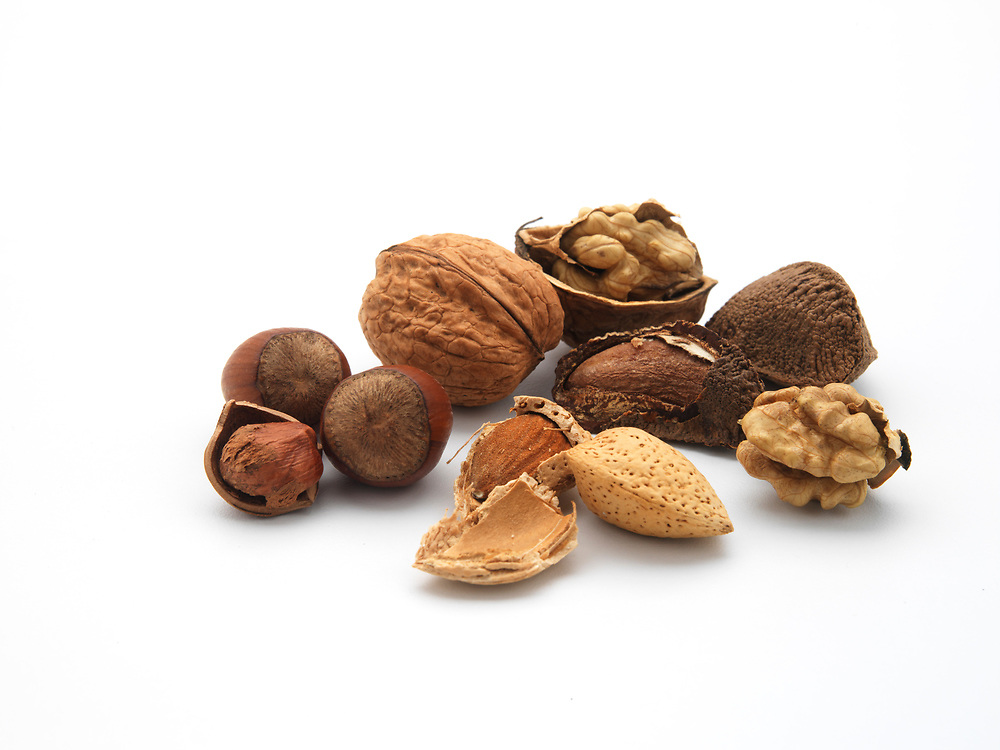 whole and cracked nuts on a white background