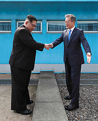 April 27, 2018 - Panmunjom, Korea - North Korean leader Kim Jong Un, left, shakes hands with South Korean President Moon Jae-in over the military demarcation line at the border village of Panmunjom in Demilitarized Zone. Their discussions will be expected to focus on whether the North can be persuaded to give up its nuclear bombs. (Credit Image: © Prensa Internacional via ZUMA Wire)