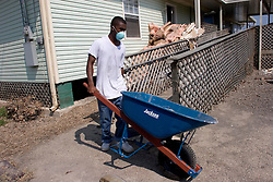 30 Sept, 2005.  New Orleans, Louisiana.  Lower 9th ward. Hurricane Katrina aftermath.<br /> The remnants of the lives of ordinary folks, now covered in mud as the flood waters remain. A young man empties a barrow full of trash from a property in the Lower 9th ward which they managed to get back to early.<br /> Photo; ©Charlie Varley/varleypix.com