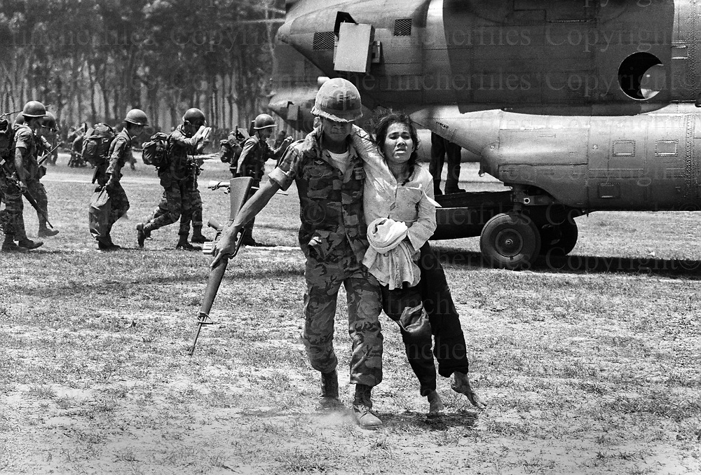 An exhausted woman is helped by a South Vietnamese soldier from a Boeing CH-47 Chinook, helicopter after the evacuation of Xuan Loc, Vietnam 1975. Evacuations near Xuan Loc in South Vietnam as the North Vietnamese army made their advance on the city. Xuan Loc was the last major battle of the Vietnam War fought between 9th and 21st April 1975. Photographed by Terry Fincher.