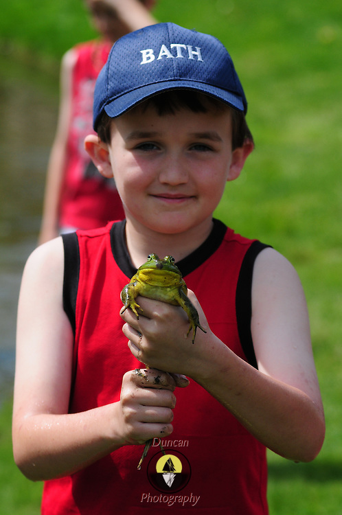 BATH -- 5/25/15 - Aleister Dowdy, 8, of Bath, holds up a frog he caught in the Library Park pond on Monday. <br /> The Memorial Day Parade in Bath took place as a result of an anonymous donor who gave $5,000 and the American Legion who donated $3,000 to pay for the parade in Bath. The Elks Club supported the parade in prior years but were unable to do so this year, leaving organizers without a funding source close to the parade date.  <br /> Photo ©2015 by Roger S. Duncan / For the Forecaster.