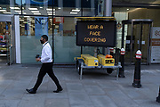 A traffic and events matrix sign tells Londoners to wear a face covering during the Coronavirus pandemic, in the City of London, on 15th September 2020, in London, England.