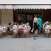 TREVISO, ITALY - AUGUST 24:  Customers sit at a cafe in the city centre on August 24, 2013 in Treviso, Italy. Treviso claims that Tiramisu was invented in the 1960s by Alba Campeol, the owner of the Restaurant called ÒAlle BeccherieÓ, who supposedly wanted to create a dessert that would give her an energy boost after the birth of her son.  (Photo by Marco Secchi/Getty Images)