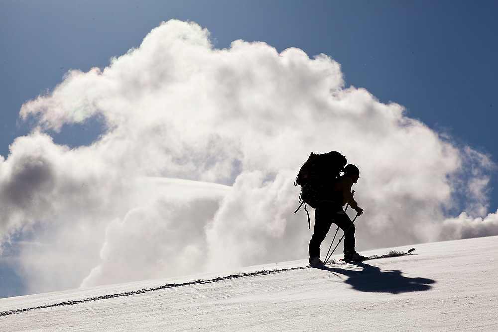 Backcountry skier Judd MacRae is silhouetted against a cloud in Uncompahgre National Forest, Colorado.