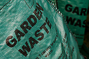 In a back south London garden (yard) we see a detail of a London borough of Lambeth council green waste recycling bag. This local authority once provided for free, up to three bags per household purely for the use of garden and plant material instead of it going to landfill. But in the era of government and economic cuts, this is one service now charged for in 2011. The stenciled lettering tells home owners that only organic waste should be put in before a fortnightly collection from the street outside.