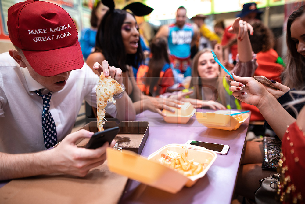 © Licensed to London News Pictures . 27/12/2018. Wigan, UK. A man dressed as Donald Trump and wearning a Make America Great Again t-shirt eats a pizza in a takeaway . Revellers in Wigan enjoy Boxing Day drinks and clubbing in Wigan Wallgate . In recent years a tradition has been established in which people go out wearing fancy-dress costumes on Boxing Day night . Photo credit: Joel Goodman/LNP