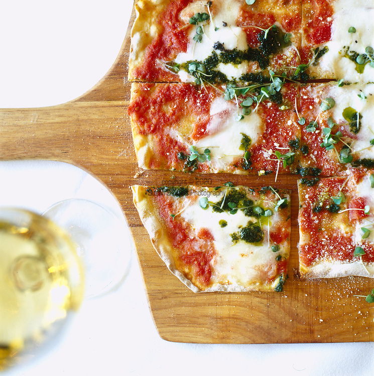 traditional vegetarian pizza served on a pizza board with tomato sauce, radish sprouts, pesto and fresh mozzarella cheese with a glass of white wine