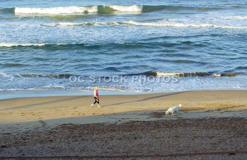 A Woman Walking Her Dog on the Beach in Huntington Beach California