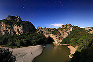 """A view on a clear, starry night of Pont d'Arc, a beautiful natural stone bridge the Ardeche river dug in the cliff. It is placed right at the beginning of the canyons, just off the nice small town of Vallon Pont d'Arc.<br /> The full moon was so bright that night that I blew off my first attempts at 1 minute f4. This is a sequence of 5 vertical frames all exposed for 30"""" at f5, and then stitched together in Photoshop."""
