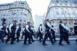"""© Licensed to London News Pictures. 19/04/2019. LONDON, UK.  Police officers march to form a cordon for the removal of the pink boat at Oxford Circus during """"London: International Rebellion"""", on day five of a protest organised by Extinction Rebellion.  Protesters are demanding that governments take action against climate change.  Police have issued a section 14 order requiring protesters to convene at Marble Arch only so that the protest can continue.  Photo credit: Stephen Chung/LNP"""