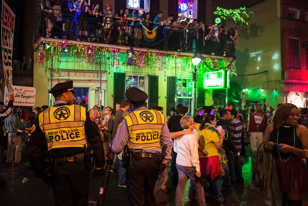 New Orleans police officers keep an eye on Mardi Gras revelers on Bourbon Street in the French Quarter.