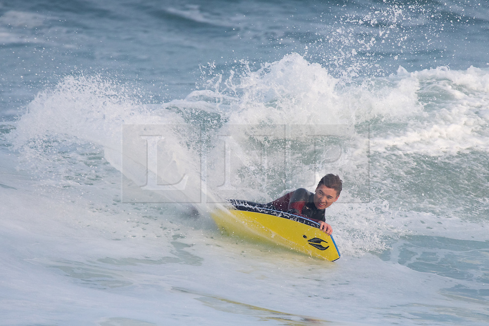 © Licensed to London News Pictures. 24/04/2020. Padstow, UK. A bodyboarder catches a wave just after sunrise near Padstow on the north coast of Cornwall. A period of warm weather is set to continue for the weekend. Photo credit : Tom Nicholson/LNP