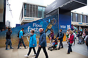 London 2012 Olympic Park in Stratford, East London. People walking past some advertising for one of the main sponsors, VISA.