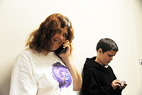 While waiting for a shower at the Chinatown Health Services Center in Salinas, Joan Sassman makes a call, and her son Nathaniel Ashlin, 11, folds a dollar bill into various shapes. By all accounts, Nathaniel is an excellent student.