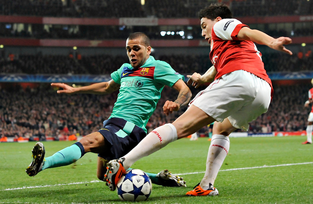 Arsenal's Samir Nasri, right, challenges for the ball with Barcelona's Daniel Alves during a Champions League, round of 16, first leg soccer match at Arsenal's Emirates stadium in London, Wednesday, Feb.16, 2011.