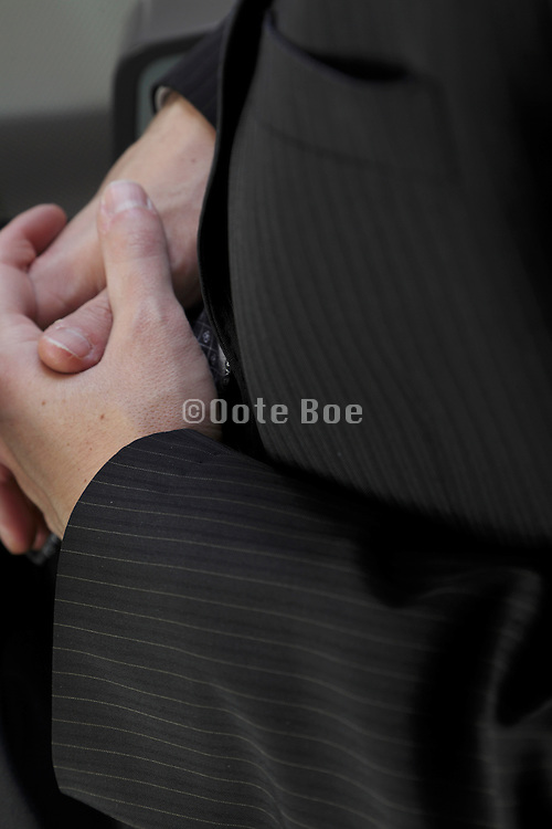 male person in business suit with folding hands sitting