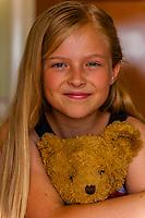Preteen Mormon girl hugging her teddy bear, Cedar City, Utah USA