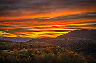 A fiery sunset lights the atmosphere above the rolling autumn mountains along the West Virginia Highland Scenic Highway.