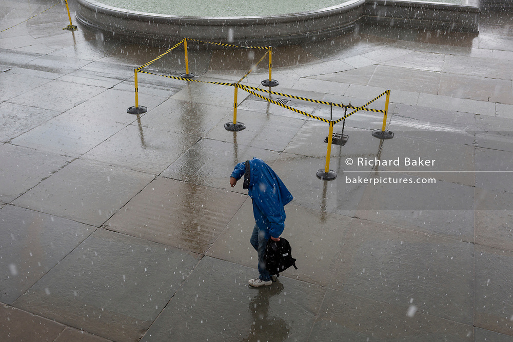 A man struggles through sudden heavy rain in Trafalgar Square, on 13th August 2018, in London, England.