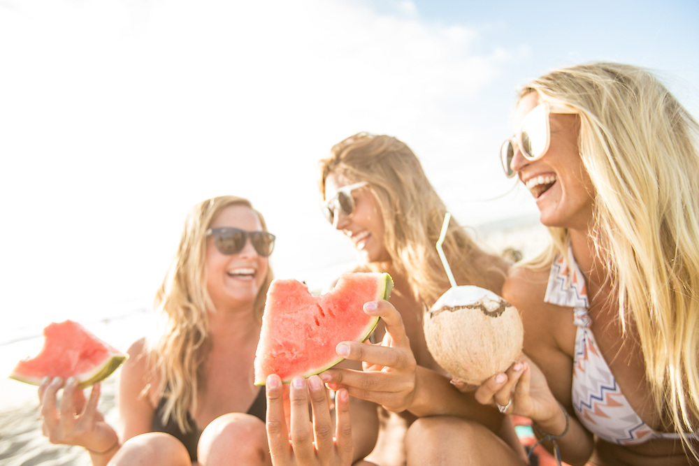 Three girls laughing and eating a watermelon at the beach in Mission Beach, San Diego, CA.