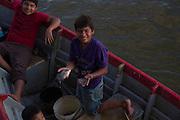 A boy shows the day's catch after fishing with his family on the San Juan River. Boca de Sábalos, El Castillo, Río San Juan, Nicaragua. January 26, 2014.