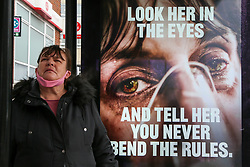© Licensed to London News Pictures. 01/02/2021. London, UK. A woman with a protective face covering stands next to government's 'Look her in the eyes - And tell her you never bend the rules.' awareness publicity campaign poster in north London. Covid-19 infection rates are continuing to drop across London. According to a Government scientific adviser, the UK could be easing out of restrictions in March and back to almost normal by summer if vaccines are 70 to 80 per cent effective at blocking transmission. Photo credit: Dinendra Haria/LNP