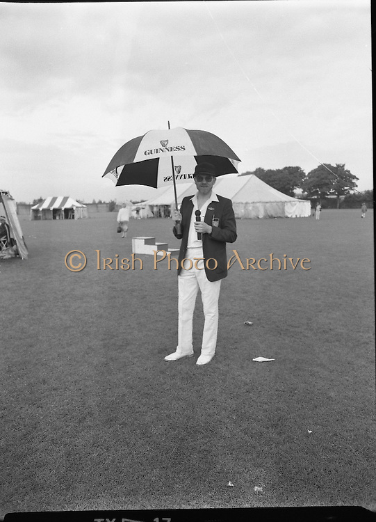 """Guinness Family Day At The Iveagh Gardens. (R83)..1988..02.07.1988..07.02.1988..2nd  July 1988..The family fun day for Guinness employees and their families took place at the Iveagh Gardens today. Top at the bill at the event were """"The Dubliners"""" who treated the crowd to a performance of all their hits. Ireland's penalty hero from Euro 88, Packie Bonner, was on hand to sign autographs for the fans...Peter the sports compere is pictured standing alone in the rain as all the competitors took shelter."""