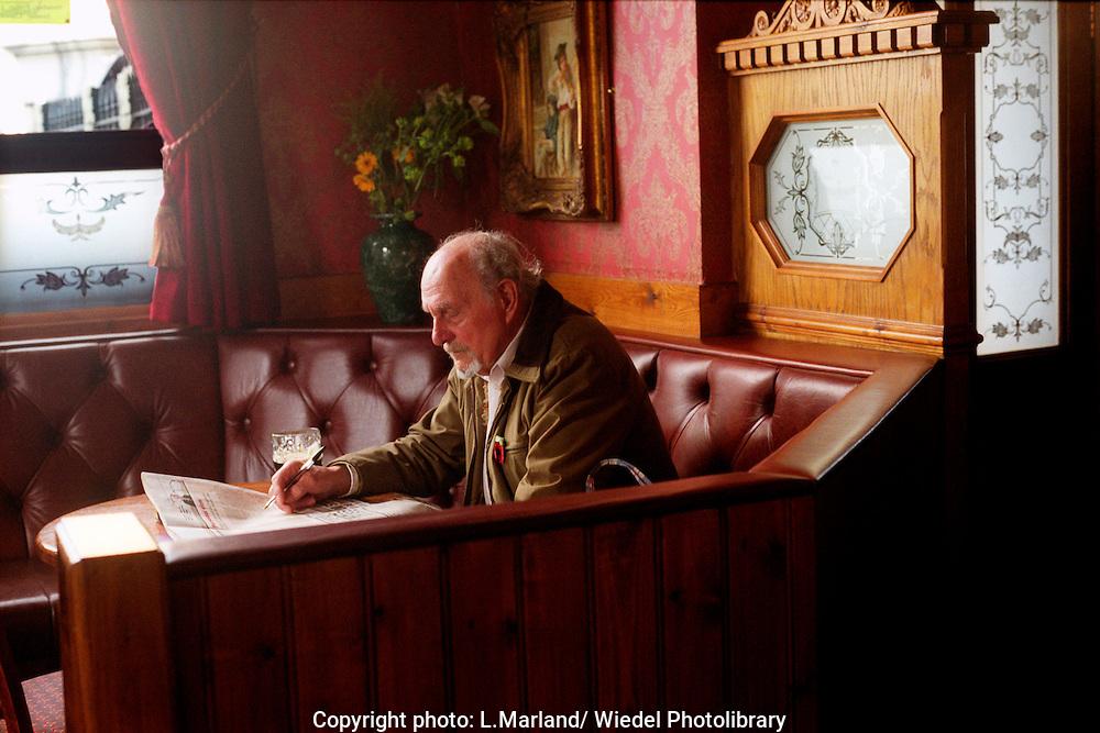 Older man sitting reading newspaper in pub.