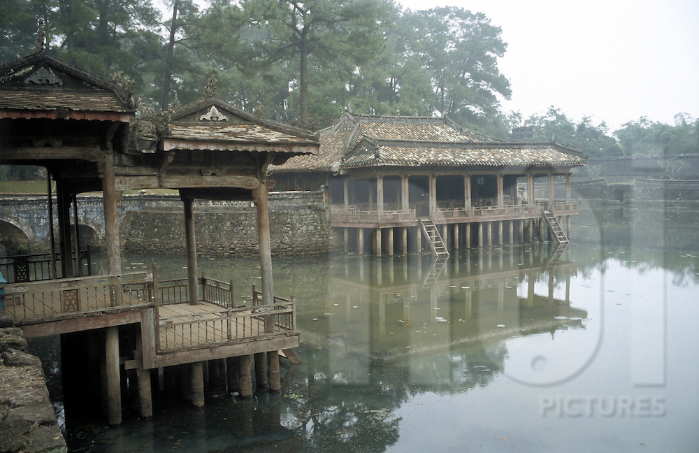 Ancient buildings hang over water within Emperor Tu Duc's Tomb complex, Hue, Vietnam, Southeast Asia